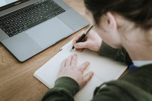 teenager writing in a journal with laptop in front of her
