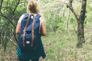 girl hiking in woods with blue backpack