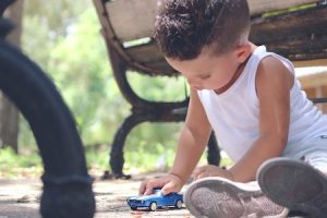 little boy in white shirt playing with a blue car at the park